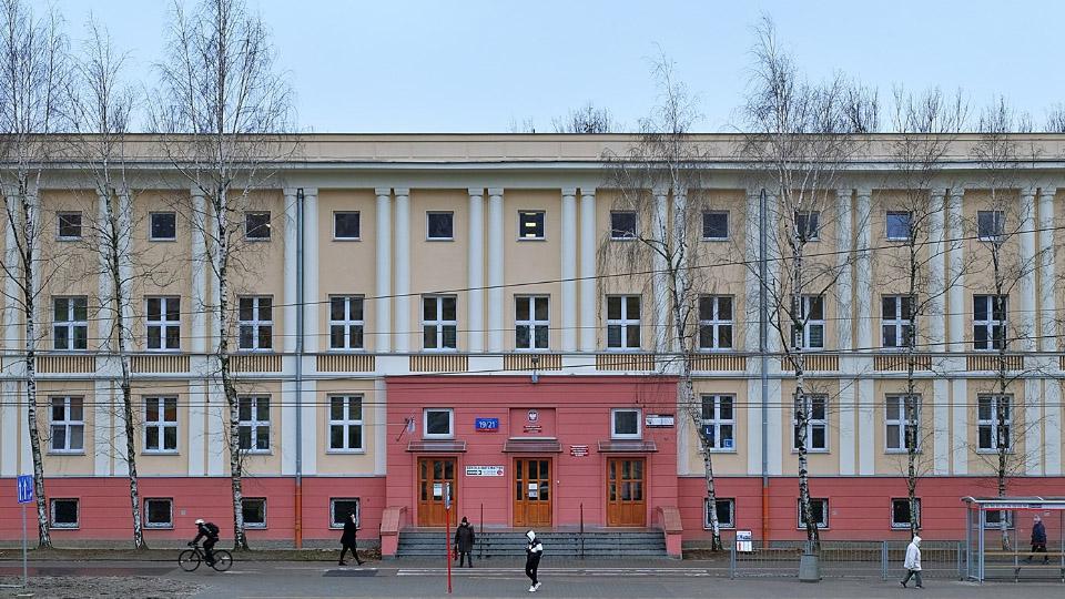 Zdjęcie przedstawia budynek Szkoły widziany od frontu, przed budynkiem rosną drzewa. Widoczni są także przechodnie.